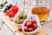 image of tumbler  - Savory small red pimento and green peppers and olives served with a tumbler of whiskey on an old rustic bar counter - JPG