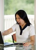 Mature Woman Expressing Extreme Anger While Looking At Her Computer Screen