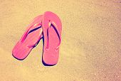 summer vacation background with a pair of sandals on a sandy beach done with a retro vintage instag