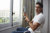 Man looking at himself in a hand mirror after rejuvenating