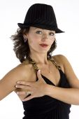 picture of halter-top  - Beautiful young woman in glamorous pose wearing black halter top and black hat against white background - JPG