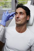 Beautiful man getting cosmetic injection to the face