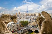 stock photo of gargoyles  - Gargoyle on Notre Dame Cathedral and city of  Paris - JPG