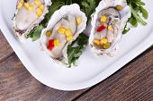 image of oyster shell  - Tasty cooked oysters in shell on wooden table - JPG