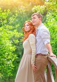 Just married, beautiful couple on wooden bridge in the park and looking up, dreaming about future, p