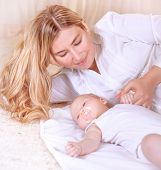 Happy young mother lying down with cute newborn baby at home, enjoying first days of parenthood, ten