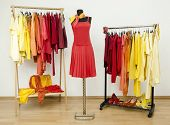 Wardrobe with yellow, orange and red clothes arranged on hangers and a red outfit on a mannequin.
