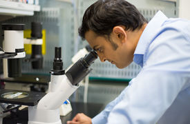 stock photo of histology  - Closeup portrait young scientist looking into microscope - JPG