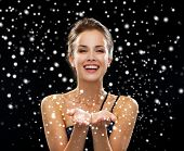 advertisement, winter holidays, christmas, people and luxury concept - laughing woman in evening dress holding something imaginary over blue snowy background