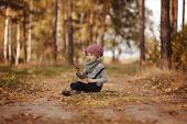 cute child girl playing with stick on the road in autumn forest