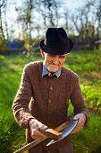 Old Farmer Sharpening Scythe