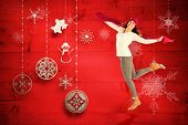 Happy brunette leaning and holding scarf against christmas decorations over wood