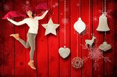 Happy brunette jumping and holding his scarf against christmas decorations over wood