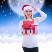 Stressed blonde in santa hat holding gifts against white clouds under blue sky
