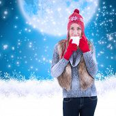 Woman in winter clothes holding a mug against blue background with vignette
