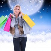 Blonde in winter clothes holding shopping bags against white clouds under blue sky