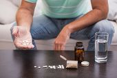 Man with his medicine laid out on coffee table at home in the living room