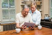 Senior couple looking at tablet pc together at home in the kitchen