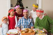 Cheerful extended family in party hat at dinner table at home in the living room