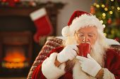 stock photo of father time  - Father christmas drinking a hot beverage at home in the living room - JPG