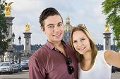 cute couple taking a selfie during a city trip to Paris, during a sight seing tour in front of one of the highlights