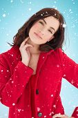 Portrait of a cheerful brunette in red coat against blue background with vignette