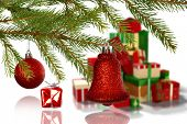 Red decorations on branch against green red and gold christmas gifts