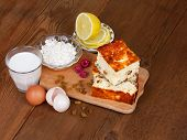 Cheese casserole with raisins and mint on plate over wooden background