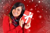 Excited brunette holding red gift against red design with white stars