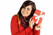 Excited brunette holding red gift on white backgorund