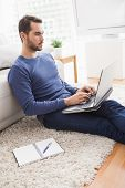 Young man sitting on floor using laptop at home in the living room