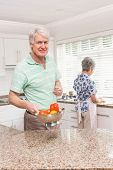 Senior man showing colander of vegetables at home in the kitchen