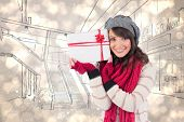 Festive brunette holding white and red gift against light glowing dots design pattern