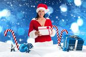 Woman smiling with christmas present against christmas scene with gifts and candy canes