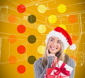 Festive blonde holding christmas gift and bag against yellow background with vignette