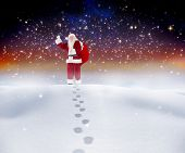 Santa walking in the snow against serene landscape