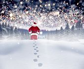 Santa walking in the snow against bright stars of energy over landscape