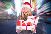 Festive blonde holding pile of gifts against blurry new york street