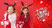 Festive little girls holding gifts against red vignette