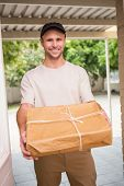 Delivery man smiling at camera offering parcel outside the warehouse