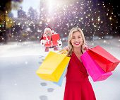 Stylish blonde in red dress holding shopping bags against santa delivering gifts in city