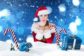 Pretty girl in santa costume blowing at camera against christmas scene with gifts and candy canes