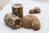 stock photo of briquette  - Brown palm sugar briquettes on crushed paper - JPG