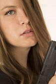 Close-up Portrait Of A Woman Holding A Pistol With A Somber Expression