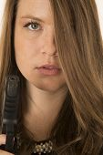 Beautiful Woman Holding A Pistol Peering Through Her Hair