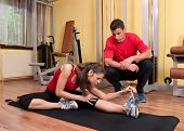 Beautiful young girl doing stretching exercises in the gym under supervision of her coach