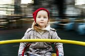 stock photo of merry-go-round  - Cute little girl rounding on merry - JPG