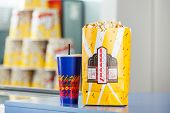 Popcorn paperbag and cold drink on concession counter at cinema