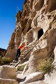 image of cave woman  - beautiful woman climbing into caves in Bandelier national Monument in New Mexico - JPG