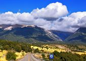 The road the Ruta 40 passes in Argentina among fields. Magnificent cumulus clouds decorate mountains of the Southern Andes